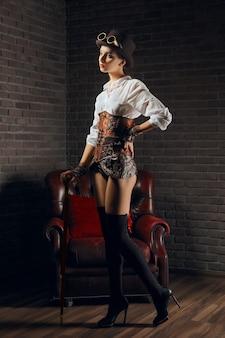 Портрет красивой девушки стимпанк в нижнем белье и чулках, шляпе и очках.