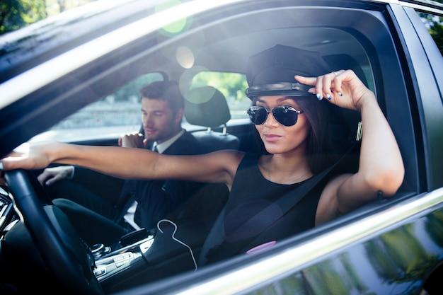 차를 운전하는 선글라스에 아름 다운 세련 된 여자의 초상화