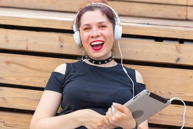 Портрет красивой стильной молодой веселой женщины в наушниках, сидя в парке в теплый летний день. концепция досуга и учебы на выходных.