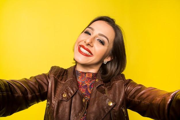 노란색 벽에 셀카를하고 아름다운 성공적인 웃는 여자의 초상화