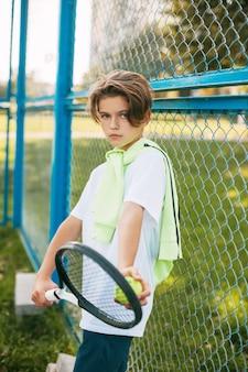 Портрет красивого подростка, стоящего с теннисной ракеткой и мячом в руках