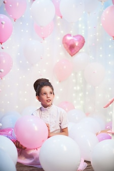 풍선의 풍경에 무성 한 분홍색 치마에 아름 다운 십 대 소녀의 초상화. 호일 및 라텍스 풍선 헬륨으로 가득합니다.