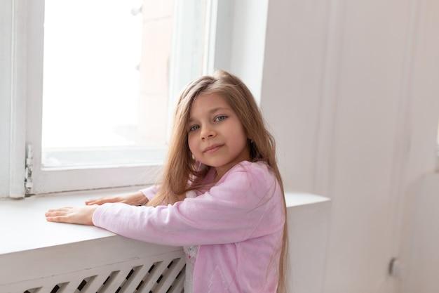 美しい10代の少女の肖像画が白い窓のそばに立っています。
