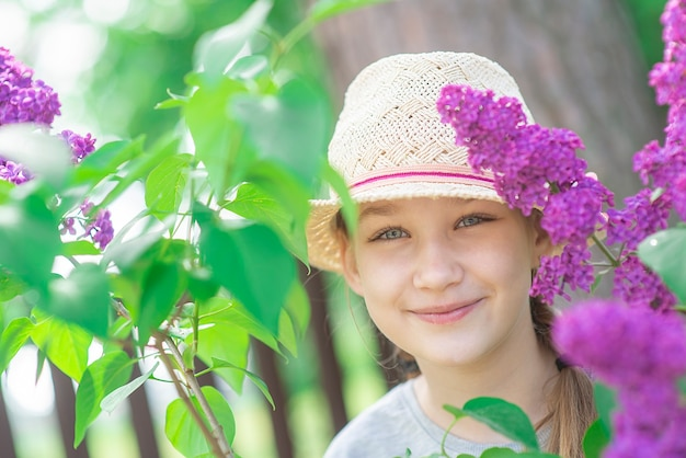Портрет красивой девочки-подростка в летней шляпе и цветущей ветке сирени