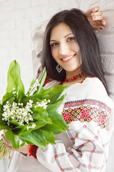 Портрет красивой украинской девушки в национальном платье с букетом цветов ландыша