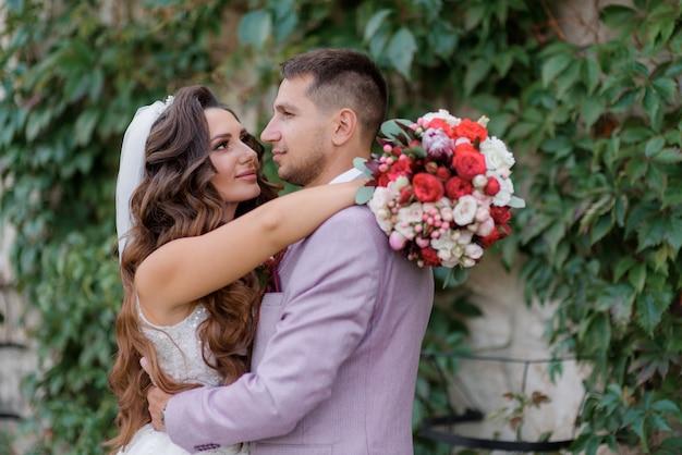 Портрет красивой пары свадьбы перед стеной покрытой зелеными листьями
