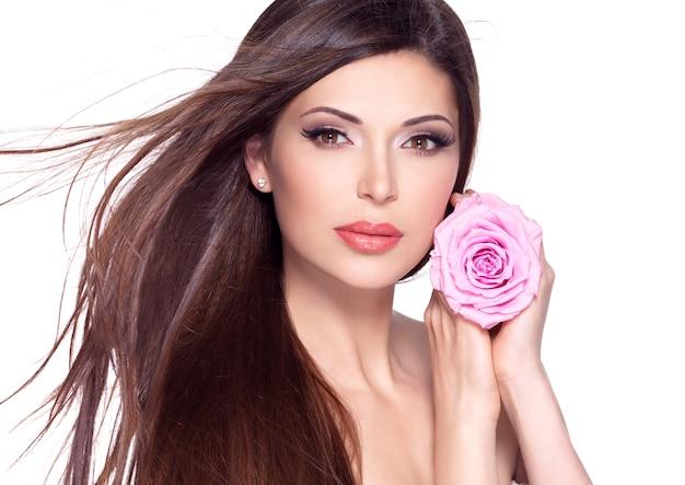 Портрет красивой белой красивой женщины с длинными прямыми волосами и розовой розой на лице.