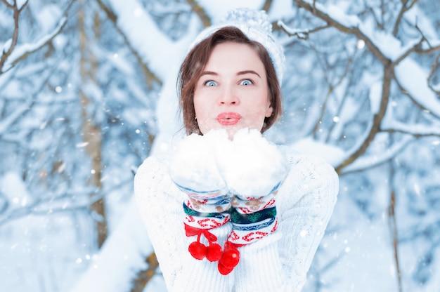 新年のミトンの冬の森を背景に美しい女性の肖像画。クリスマスのコンセプト、冬のお祝い、森の中の散歩、休暇。ミクストメディア
