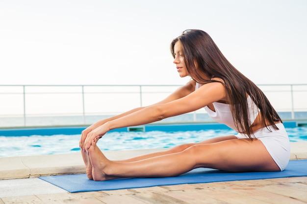 屋外でストレッチ体操をしている美しい女性の肖像画
