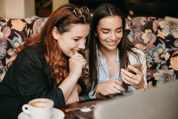 Портрет красивой женщины, держащей смартфон и смотрящей на экран, улыбаясь, в то время как ее подруга тоже улыбается экрану смартфона.