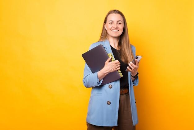Портрет красивой женщины, держащей ее ноутбук, журнал и телефон, готовые к работе.