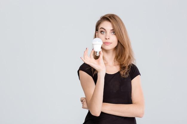 흰색 배경에 고립 된 전구를 들고 아름 다운 여자의 초상화