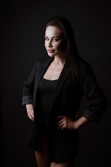 暗い背景でポーズをとって黒いボディスーツとジャケットの美しい女性の肖像画