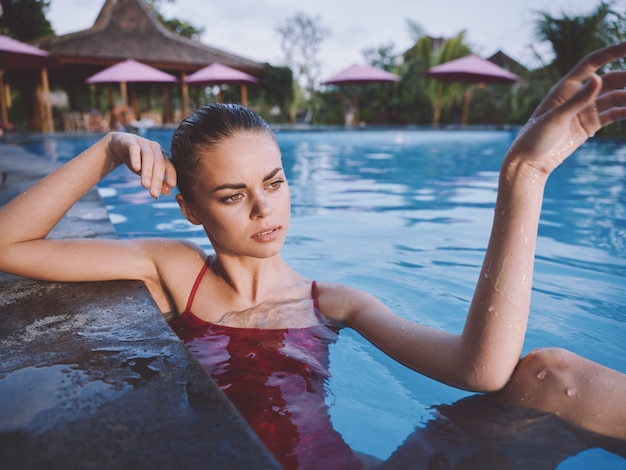 彼女の手で身振りで示すスイミングプールの透明な水で美しい女性の肖像画