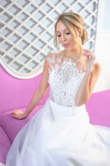美しいメイクとソファの上の髪を持つ白いウェディングドレスで美しい女性の肖像画