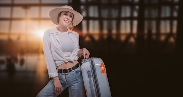 Портрет красивой женщины в желтой шляпе, стоящей в аэропорту с чемоданом. концепция путешествия. смешанная техника