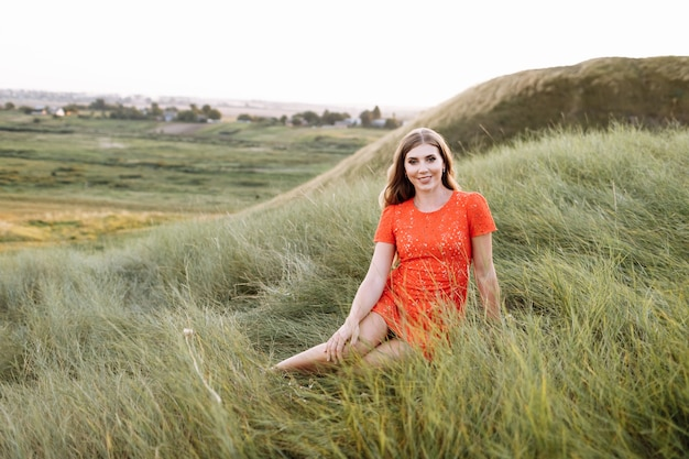 아름 다운 여자의 초상화는 필드에 푸른 잔디에 앉아있다