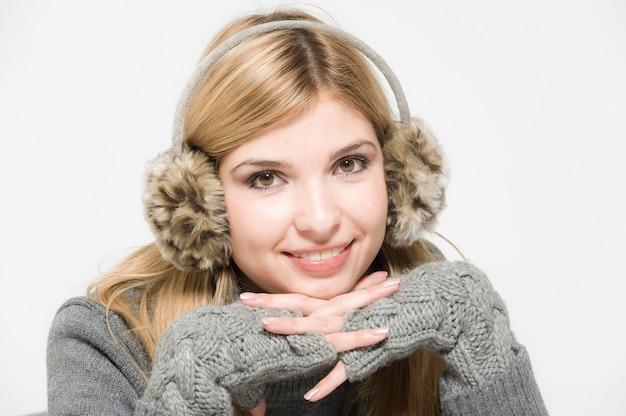 毛皮のヘッドフォンで白い背景の上の美しい女性の肖像画