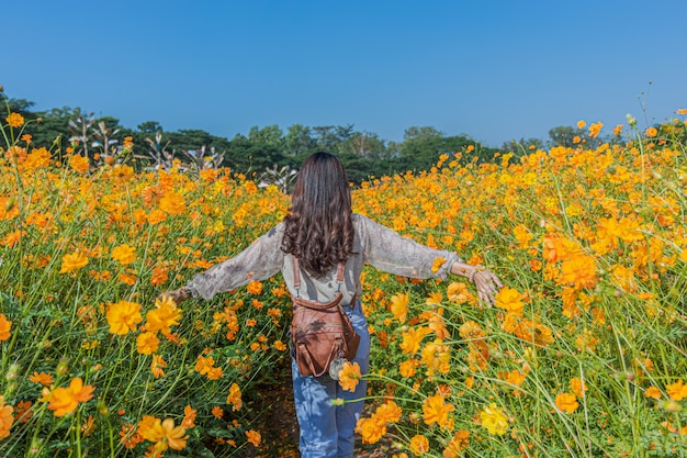 아름 다운 여자의 초상화 사진 촬영을 위해 포즈 짐 톰슨 농장에서 노란 꽃밭을 방문