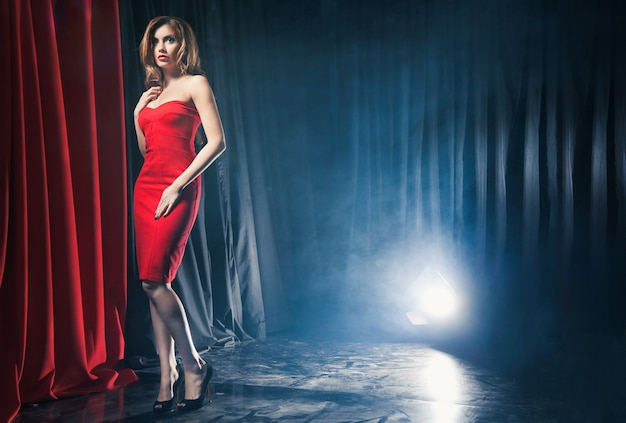 Портрет красивой женщины, позирующей в красном платье перед сценами