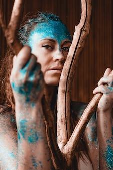 野生の森のようにポーズをとる美しい女性の肖像画。彼女の顔に青い輝きを持つ女性。人は他の人とは異なります。個性