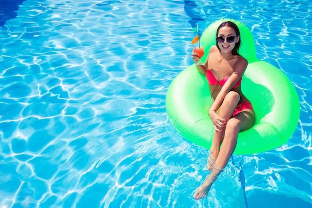 Портрет красивой женщины, отдыхающей на надувном матрасе в бассейне