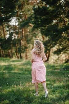 美しい女性の肖像画は、夏の日の休暇で野原、自然の緑の芝生に逃げます。日没時に公園で遊ぶ。閉じる。