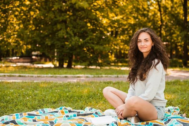 Портрет красивой женщины, сидящей на одеяло