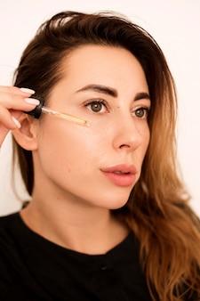 Портрет красивой женщины, которая увлажняет кожу. она подносит его к лицу, а затем втирает в кожу.
