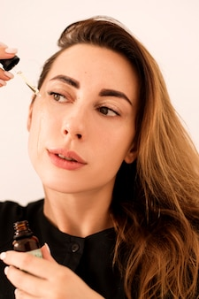 Портрет красивой женщины, которая увлажняет кожу. кожа после процедуры сияет.