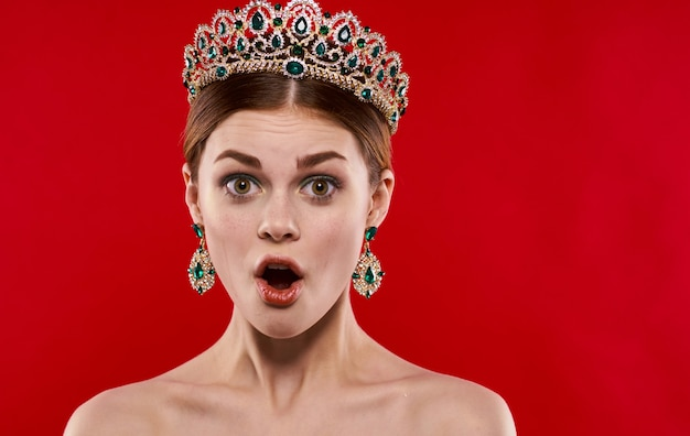 赤い背景の上の彼女の頭に王冠を持つ美しい女性の肖像画。高品質の写真