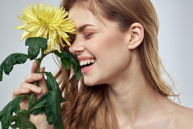 光の魅力的な笑顔モデルの赤い髪に黄色い花を持つ美しい女性の肖像画