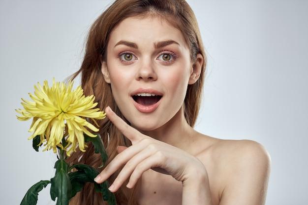 モデルでトリミングされたライトに黄色い花を持つ美しい女性の肖像画