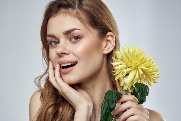 가벼운 벽에 노란색 꽃과 함께 아름 다운 여자의 초상화 매력적인 미소 모델 빨간 머리.