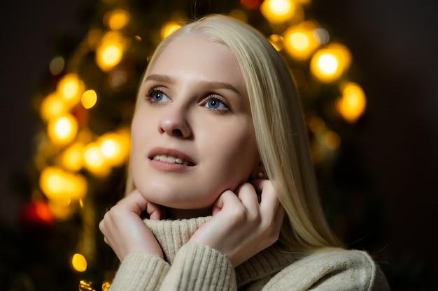 장식 된 크리스마스 트리 근처에 금발 머리를 가진 아름 다운 여자의 초상화, 그녀는 흰색 니트 스웨터를 입고