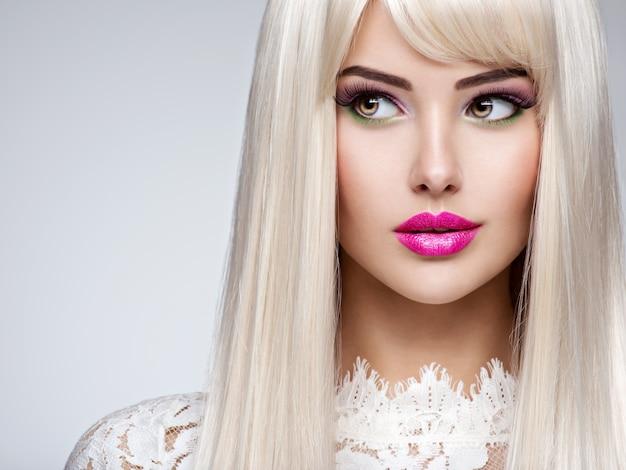 Портрет красивой женщины с длинными белыми прямыми волосами и ярким макияжем. лицо фотомодели с розовой помадой. красивая девушка позирует.