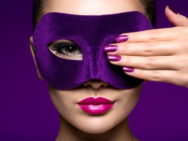 보라색 손톱과 얼굴에 보라색 극장 마스크와 아름 다운 여자의 초상화.