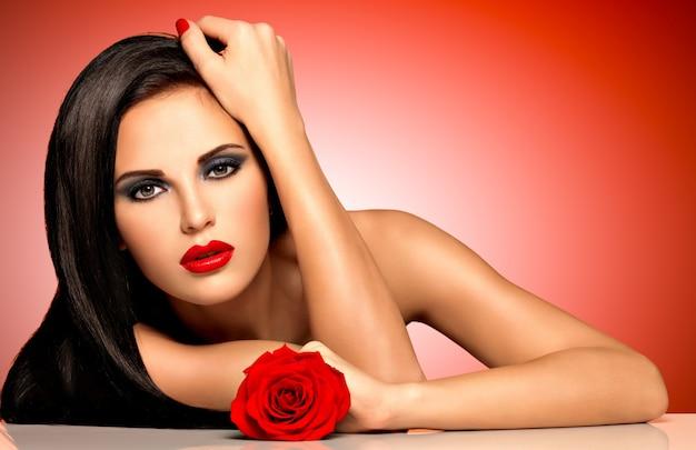 赤い唇を持つ美しい女性の肖像画は、バラを手に持っています。赤い背景の上にスタジオでポーズをとって長い髪のファッションモデル