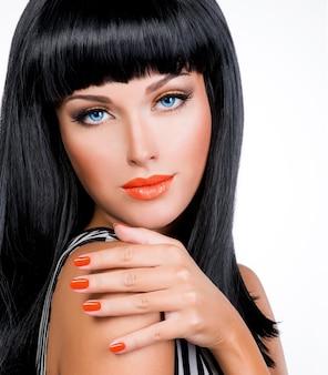 Портрет красивой женщины с красными ногтями, гламурным макияжем и длинными черными волосами