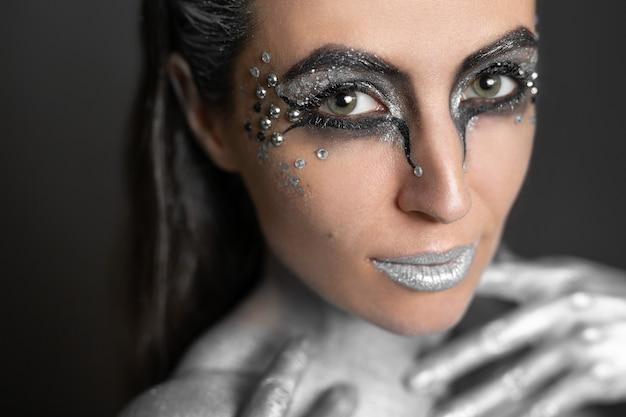 肌と髪に銀色の絵の具を塗った美しい女性のポートレート。