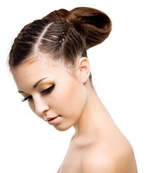 ピグテールのスタイルの髪型を持つ美しい女性の肖像画。空白の上