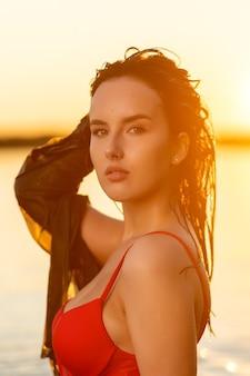 바다와 일몰을 배경으로 섹시한 빨간 비키니를 입고 젖은 머리를 한 아름다운 여성의 초상화. 열 대 해변에서 세련 된 세련 된 젊은 여자