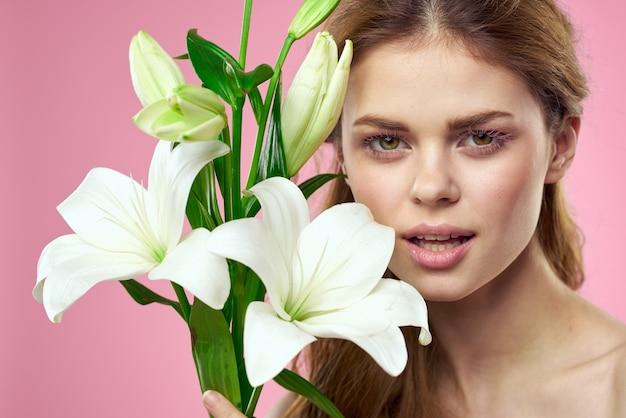 Портрет красивой женщины с белыми цветами в руках на розовом фоне copy space обрезанный вид. фото высокого качества