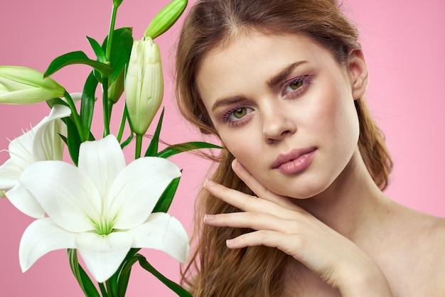 ピンクの背景に白い花を手に美しい女性の肖像画コピースペースのトリミングされたビュー