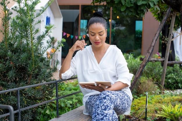 Портрет красивой женщины, пишущей в книге, сидят, думая о работе в парке, расслабьтесь на открытом воздухе.
