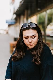 街の通りの暖かいセーターで美しい若い大人の女の子の肖像画