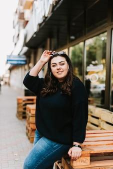 街の通りの背景に暖かいセーターを着た美しい若い大人の女の子の肖像画