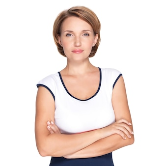 Портрет красивой молодой взрослой белой серьезной женщины со скрещенными руками над белой стеной