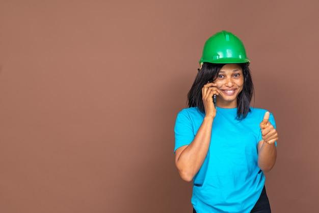 聞いた帽子をかぶって、電話をかけ、無地の背景に立って、親指を立てるジェスチャーをする美しい若いアフリカの女性建設労働者の肖像画
