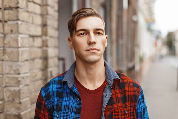 れんが造りのヴィンテージの建物の近くの髪型を持つ美しい若いアメリカ人の男の肖像画。